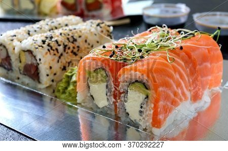 Sushi Restaurant Menu. Set Of Sushi Rolls, Sauce, Wasabi And Hand With Chopsticks On Dark Background