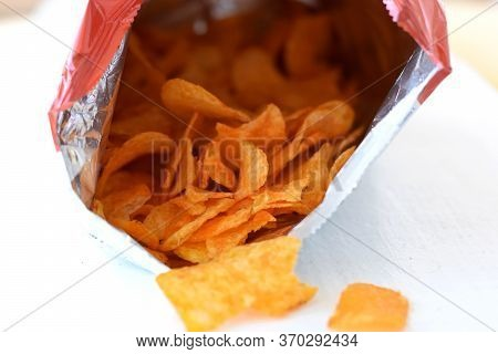 Potato Chips Lying In Front Of A Chips Bag Against White Background/ Salty Potatoes Chips/ Unhealthy