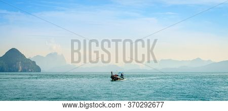 Krabi, Thailand, November 7, 2017: Traditional Thai motor boat in the Andaman Sea with Krabi coastline in the backdrop