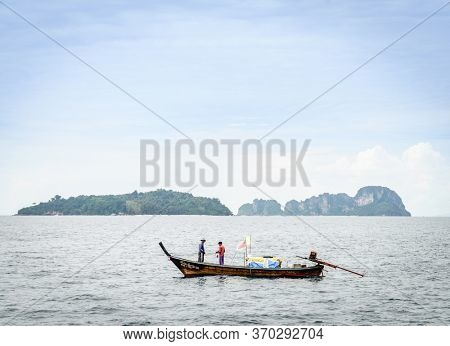 Krabi, Thailand, November 9, 2017: Thai long tail fishing boat in the Andaman Sea with islands on the horizon