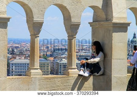 A Beautiful Girl Sits On The Fence On Trinity Square In Budapest And Enjoys A Picturesque View Of Th