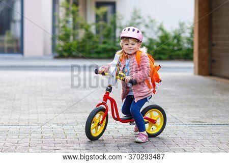 Little Happy Toddler Girl On First Day Going To Playschool Daycare. Healthy Baby On Pushing Bike To