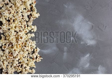 Border Of Fresh Popcorn On Grey Stone Background. Top View