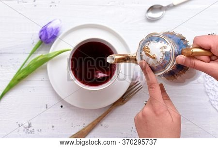 Fresh Blue Tulip And Cup Of Red Herbal Tea/ Woman Pours Hot Red Tea In A Cup On A White Wooden Table