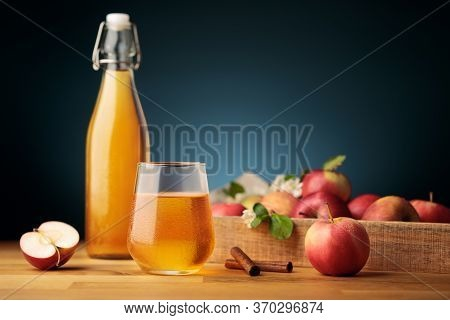 Glass Of Homemade Apple Cider Or Juice, Red Fresh Apples From The Garden And A Bottle On Background