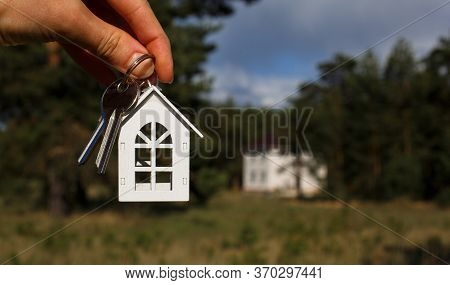 Wooden Key Chain And Keys In Hand On The Background Of An Unfinished House. Dream Of Moving, The Cot