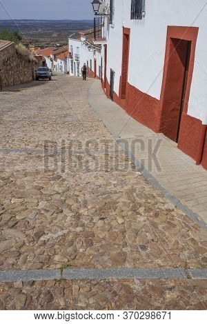 Trekker Going Down A  Steep Street Of Hornachos, Spain. Rural And History Tourism In Extremadura