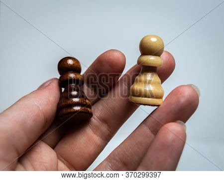 The Hand Holds Two Chess Pieces. Two Pawns On A White Background