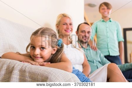 Smiling American Parents With Two Children Posing In Home Interior
