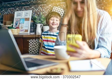 Mother Working From Home And Online Education With Kid. Stressed With Computer And Phone. Child Make