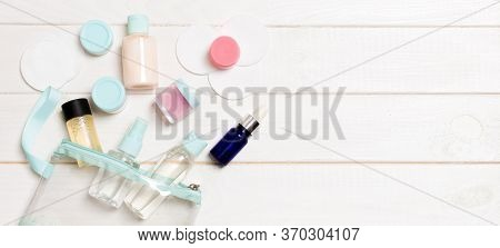 Set Of Travel Size Cosmetic Bottles On White Wooden Table Background. Flat Lay Of Cream Jars. Top Vi