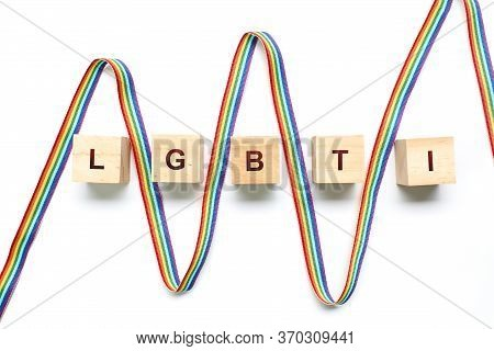 Ribbon With The Rainbow Flag Between Wooden Blocks Forming The Word Lgbti On A White Background. The