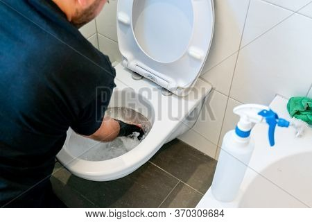 Professional Cleaner Removing Grime And Lime Scale In A Toilet Bowl During A Spring Cleaning Of An A
