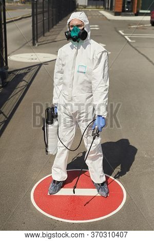 Vertical Full Length Portrait Of Male Worker Wearing Hazmat Suit And Holding Disinfecting Gear While