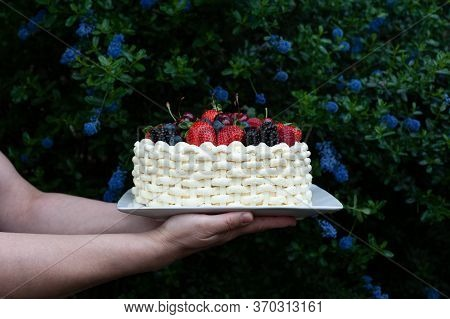 Woman Holding Plate With Beautiful Summer Cake Decorated With Berries Against Flowery Background.