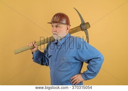 Male Bricklayer In Hard Hat With Pickaxe. Construction Worker Holds Pickaxe. Man Contractor With Axe