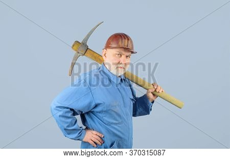 Male Miner Worker In Coveralls With Pickaxe. Construction And Building Works. Bearded Man In Uniform