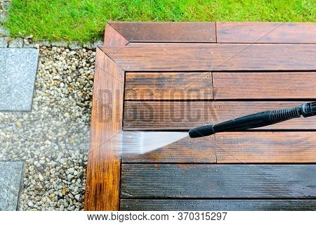 Cleaning Terrace With A Power Washer - High Water Pressure Cleaner On Wooden Terrace Surface - Focus