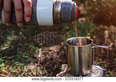 In A Camping Mug Pours Tea From A Thermos In Nature.