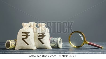 Indian Rupee Money Bags And Magnifying Glass. Profitable Investment, Dividends Payouts. Financial Mo