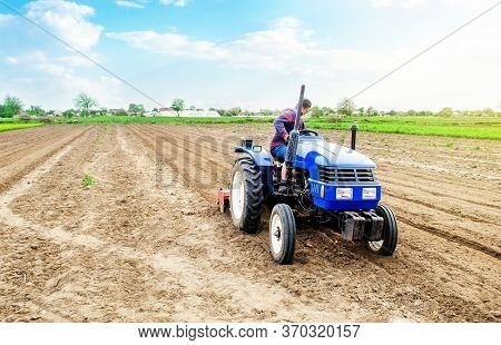 A Farmer Riding A Tractor On A Farm Field. Farming And Work In The Agricultural Industry. Cultivatin