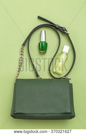 Handbag Green Color And Disinfection Gel On Green Background.  Monochrome. Vertical Format.