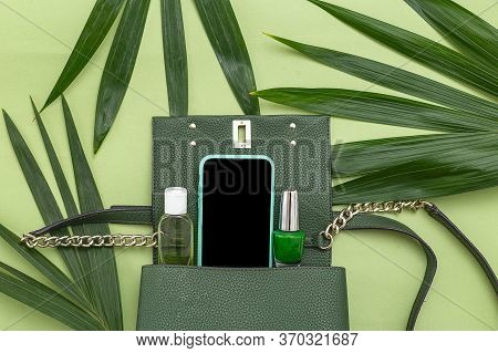 Handbag, Phone, Nail Polish And Natural Leaves On Green Background. Monochrome. Top View