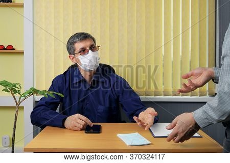 Boss Sits At A Table In The Office And, In A Conversation With An Employee, Invites Him First Of All