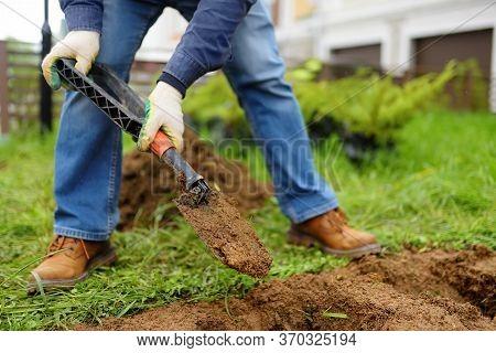 Man Diging Holes A Shovel For Planting Juniper Plants In The Yard. Seasonal Works In The Garden. Lan