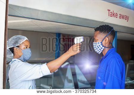 African woman working at a shop, using a mask for protection, registering and checking temperature of the customers with an infrared thermometer