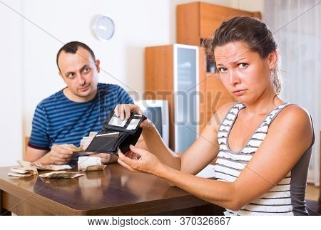 Sad Young Woman And Her Husband Counting Money For Paying Debts.