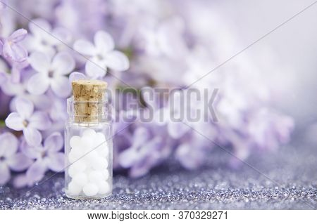 Homeopathic Globules In Glass Bottle, Close-up On A Background Of Lilac Flowers. Selective Focus. Al