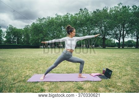 Young Woman Doing Yoga In The Green Morning Park. Girl Watching Yoga Lesson In Computer. Relax Yoga