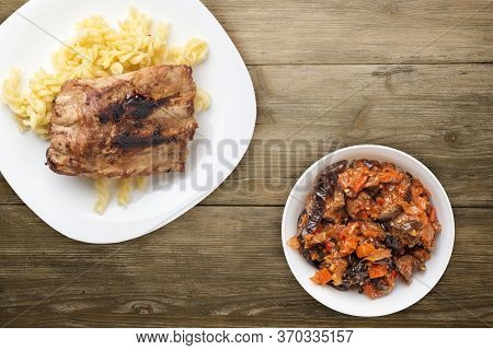 Grilled Pork Ribs With Pasta. Grilled Pork Ribs On A White Plate On A Wooden Background. Grilled Por