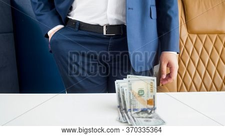 Stylish Wealthy Businessman In Blue Suit Looking On Wad Of Money