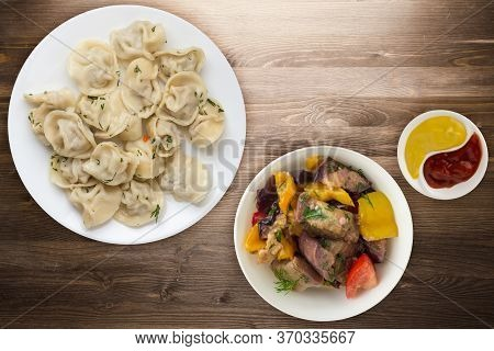 Dumplings On A White Plate On Brown Wooden Background .boiled Dumplings With Salad.meat Dumplings To