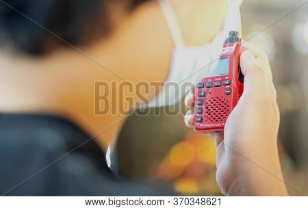 The Male Hand Holding With A Red Walkie Talkie Or Portable Radio Transceiver For Communication.