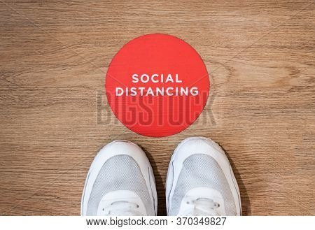People Standing On The Wooden Ground Nearby Social Distancing Word And Logo, With White Shoes And To