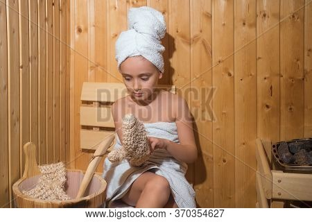 Little Girl In A Sauna With A Wooden Bucket Of Water