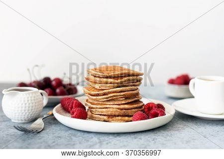 Healthy Oat Pancakes With Berries And Syrup On Table, White Background, Copy Space For Text. Vegetar
