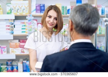 Front View Of Cheerful Pretty Woman Wearing White Lab Coat Working In Chemists Store With Male Custo