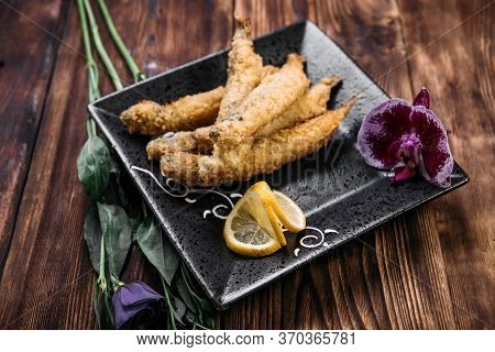 Closeup On Deep-fried Capelin With Slices Of Lemon In A Black Plate On The Wooden Table, Horizontal