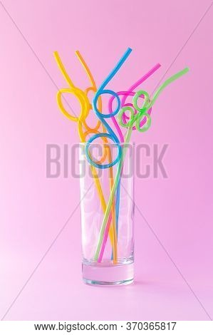 Glass With Many Plastic Colorful Cocktail Straws On A Pink Background, Fun Mood Concept. Abstraction