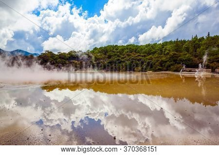 Cumulus clouds are picturesquely reflected in the smooth surface of hot water. Wai-O-Tapu Geyser Park. New Zealand, North Island. The concept of exotic, ecological and photo tourism