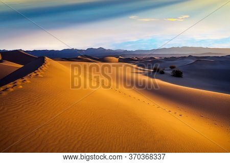 Mesquite Flat Sand Dunes - dunes in Death Valley. The morning. The sand lies in light waves. Human footprints visible along the crest of the dune. The concept of extreme and photo tourism
