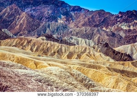 Magnificent landscape in multicolor sunset. Desert at the dry lake bottom - Death Valley in California. Zabriskie Point. USA. The concept of active, extreme and photo tourism