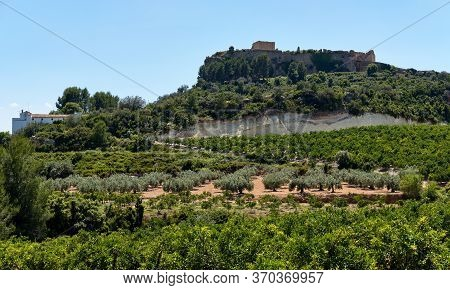 Montesa Castle Located On Hillside Against Blue Sky View, Church And Museum Inside, Agricultural Fie