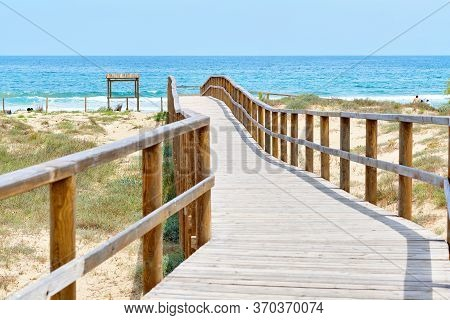 Wooden Empty Board Walk Leading Through Sandy Dunes To Mediterranean Sea And Beach Of Los Arenales D