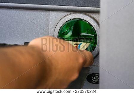 Man Hand Using Visa Credit Card At Banca Transilvania Atm. Depositor Withdraws Money From Atm Cash M