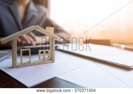 Real Estate Agent Or Realtor Calculating Price Of House In Purchase Agreement Behind The Home Archit